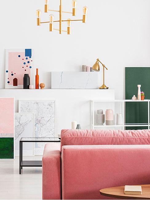 nowoczesny salon z różową sofą z aksamitu i jasnymi abstrakcyjnymi dekoracjami w stylu memphis