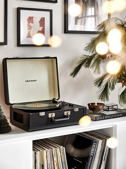 piosenki świąteczne: Ciemny gramofon, na białym stoliku, obok drzewko świąteczne z lampkami