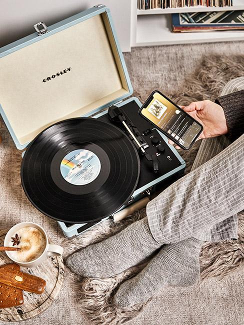 Gramofon z płyta winylową na łóżku obok człwoieka w skarpetkach i telefonem w dłoni