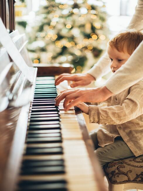 Dziecko i dorosły grający razem na fortepianie w tle choinka