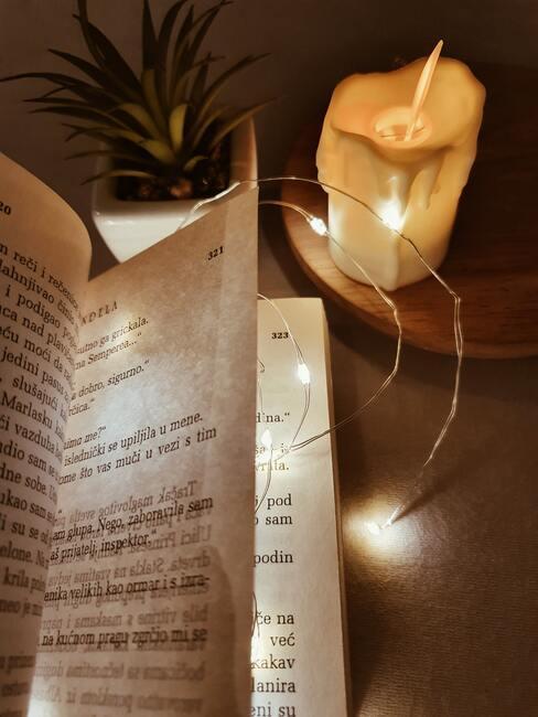 piosenki świąteczne: kartki książki z piosenkami, obok świeczka i lampki