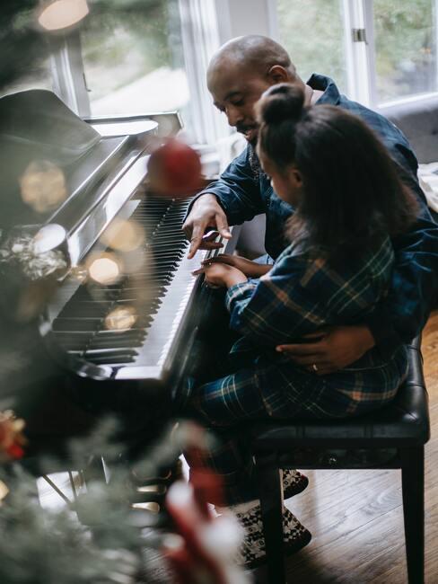 Dziadek z wnuczkiem siedzący przy fortepianie