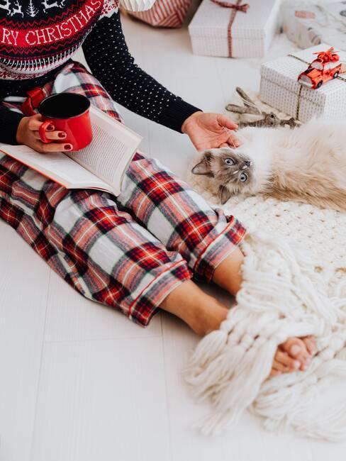 Osobą siedząca na łóżku w piżamie w kratę, z kubkiem i książką w ręku, obok leży biały kot