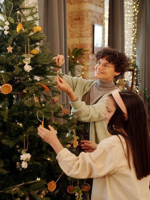 Dekorowanie choinki przez młode dziewczyny, które czują magie świąt