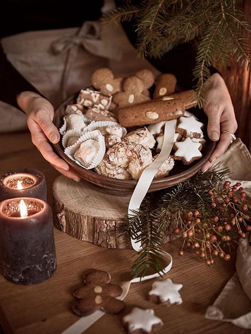 Pierniczki ozdobione lukrem w drewnianej misce na drewnianym stole