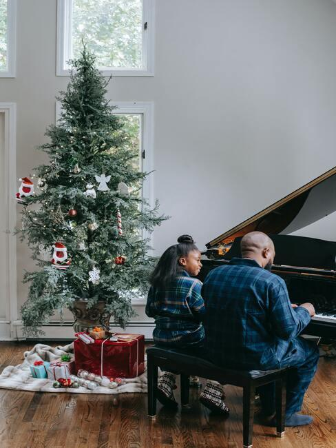 tradycje bożonarodzeniowe: Dziadek z wnuczką siedzący przy fortepianie obok choinki, śpiewający kolędy
