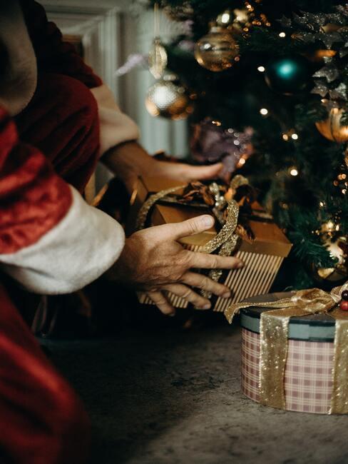 Ręce Mikołaja w których trzyma prezent i kładzie go pod choinką