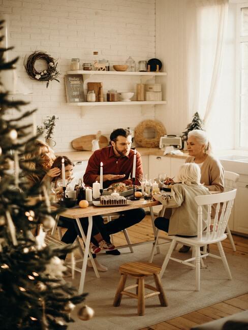 tradycje bożonarodzeniowe: dwie osoby siedzące przy stole obok choinki