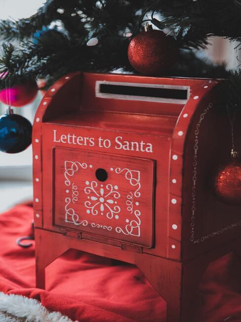 Czerwona skrzynka na listy do świętego mikołaja położona pod choinką