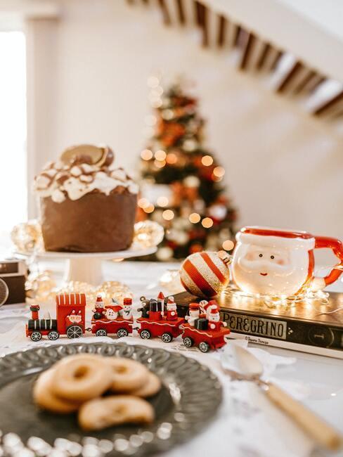 tradycje bożonarodzeniowe: stół wigilijny zastawiony zabawkami i ciastami bożonarodzeniowymi