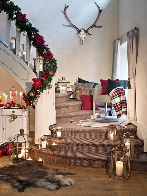 tradycje bożonarodzeniowe: schodu ustrojone na święta, girlanda na poręczy z gałązek i czerwonych kwiatów, świeczki na schodach