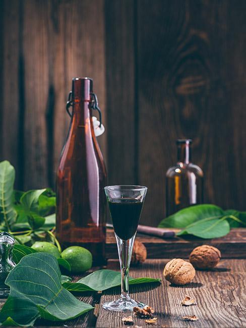 Ciemna nalewka z orzecha włoskiego w kieliszku na drerwnianym stole obok orzechów z ciemną butelką w tle