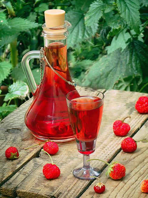 Butelka z nalewką z truskawek na drewnianym stole na tle krzewu