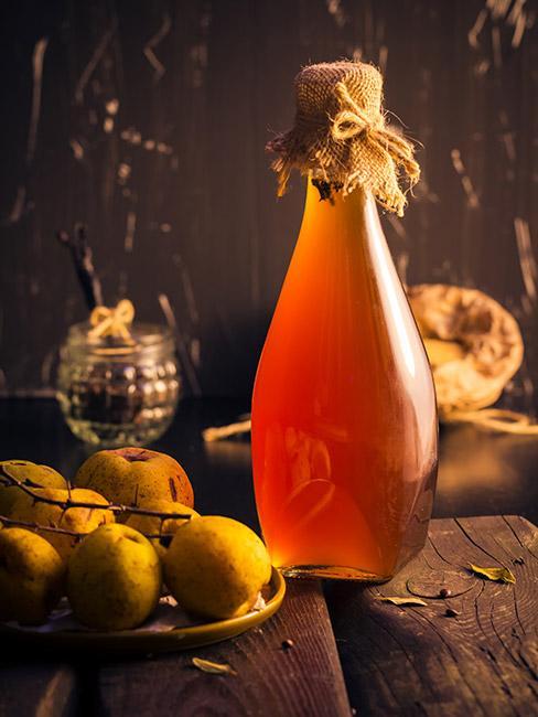 butelką z nalewką z pigwy w bursztynowym kolorze na drewnianym stole obok owoców pigwy