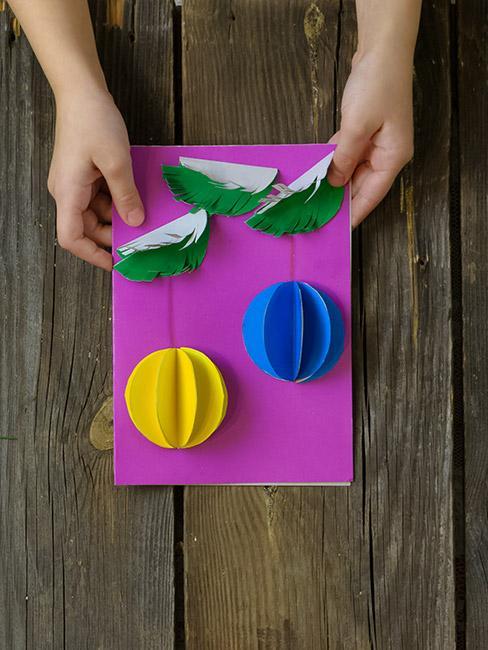 fioletowa kartka świąteczna DIY z bombkami z papieru w żółtym i niebieskim kolorze