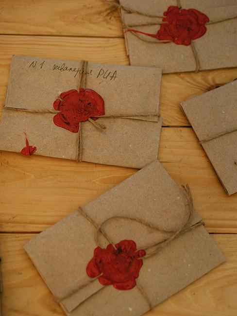 Kartki świąteczne w kopertach obwiązane sznurkiem ze stęplem z laki