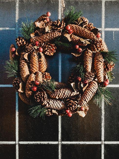 wieniec świąteczny na ścianie z szyszkami