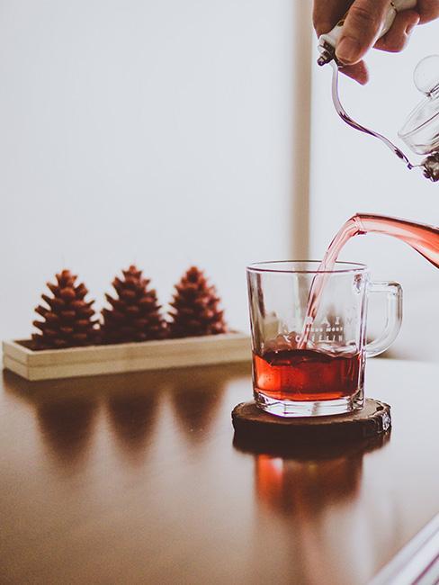 dekoracja z szyszek na stole z herbatą zimową
