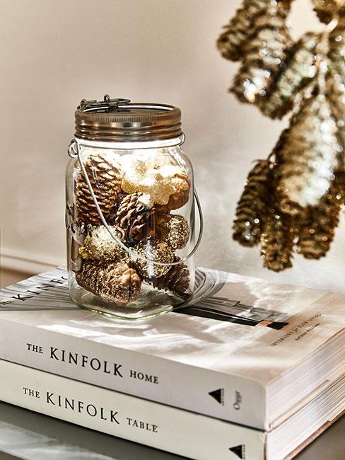 lampion świąteczny ze słoika z szyszkami i lampkami na książkach na komodzie