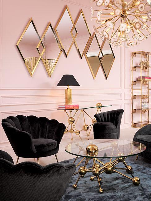 Salon w stylu art deco z czarnymi fotelami z aksamitu i lustrami w geometrycznych kształtach na jasnoróżowej ścianie