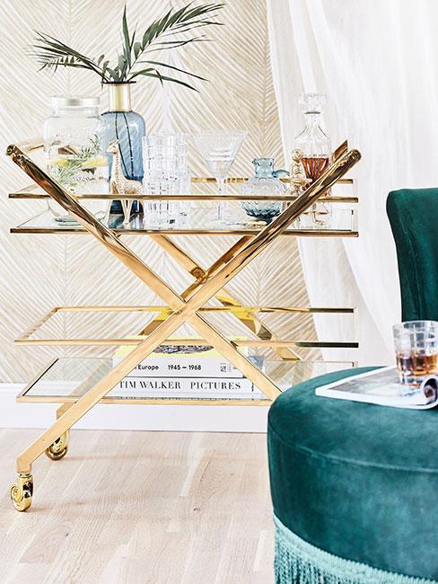 złoty wózek barowy w stylu art deco przy zielonym fotelu z frędzlami