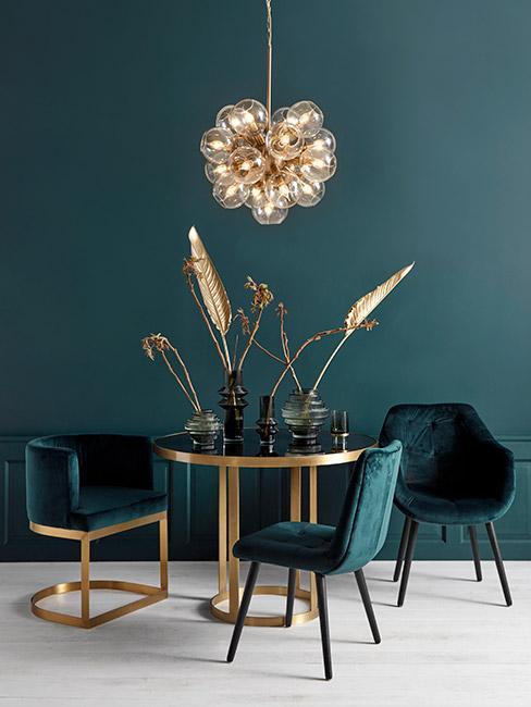 jadalnia z okrągłym złotym stołem na tle zielonej ściany w stylu art deco
