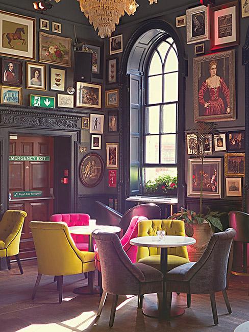 pub w stylu wiktoriańskim z kolorowymi tapicerowanymi krzesłami i oprawionymi obrazami na ścianach