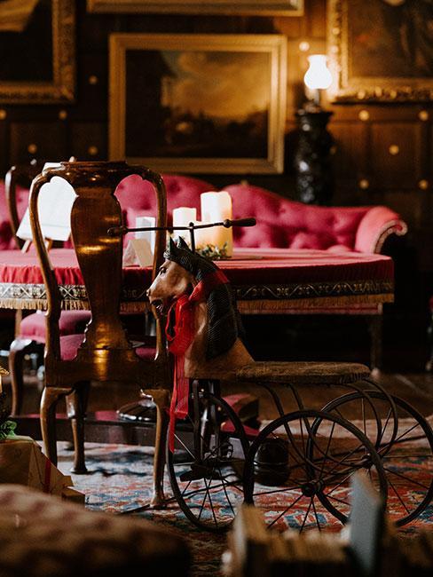 Salon w stylu wiktoriańskim z meblami w kolorze czerwonymi i zabawkami dziecięcymi z drewna