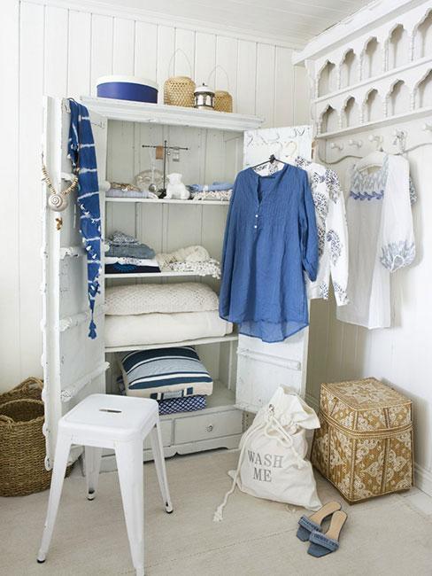 Biała szafa z białymi i błękitnymi strojami w stylu marynistycznym