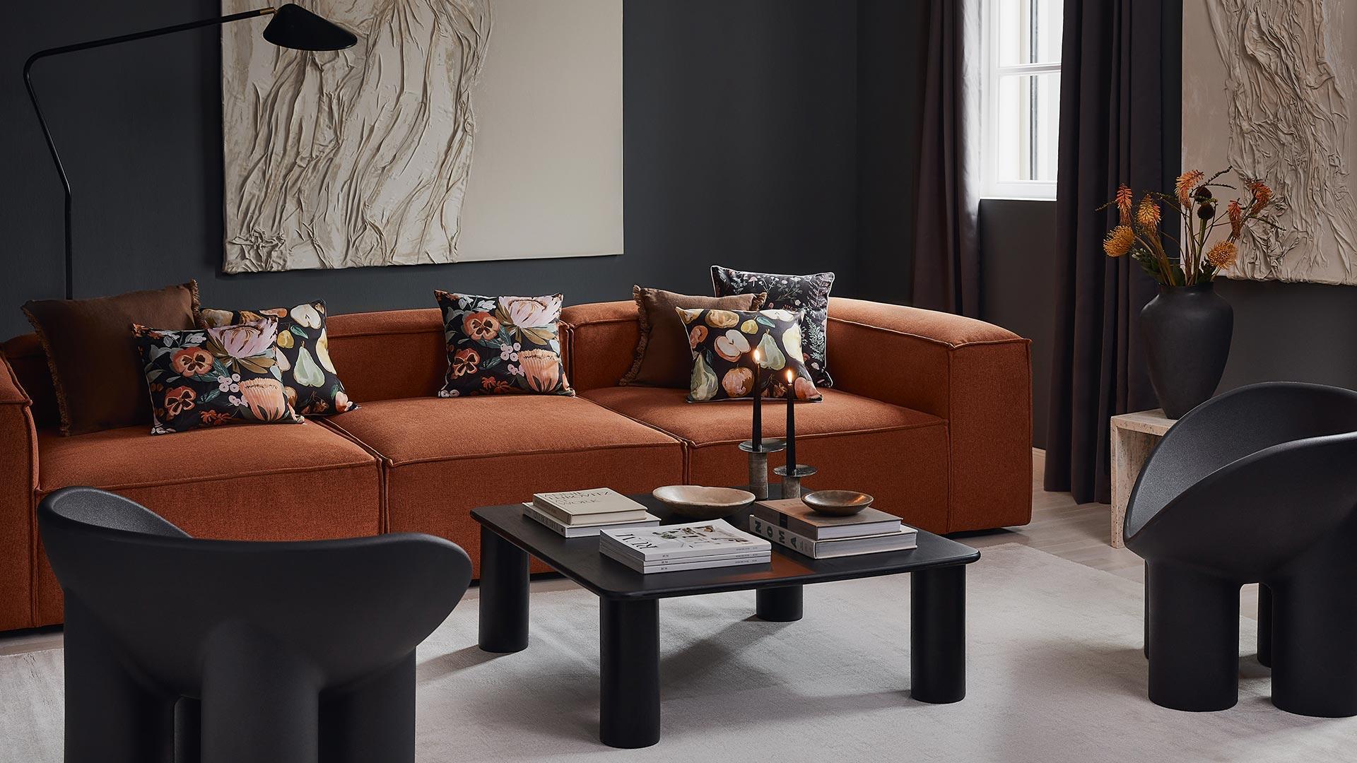 Tło na zoom ze zdjęciem salonu z pomarańczową sofą i kolorowymi poduszkami