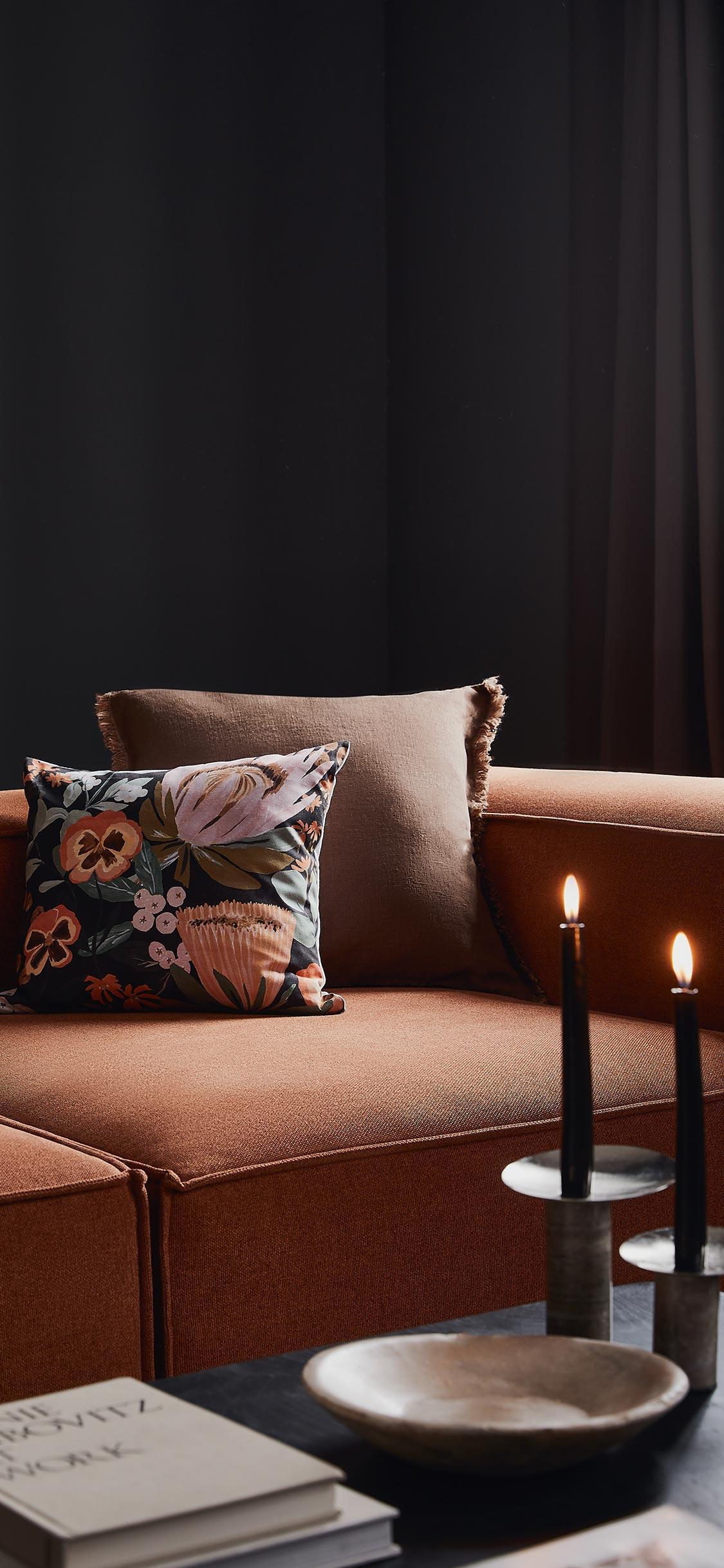 Tło na telefon ze zdjęciem ciemnego salonu z pomarańczową sofą i kolorowymi poduszkami