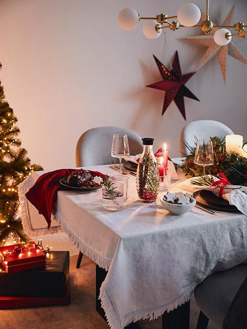 Stół wigilijny w salonie w odcieniach czerwieni i zieleni z lnianym obrusem na stole