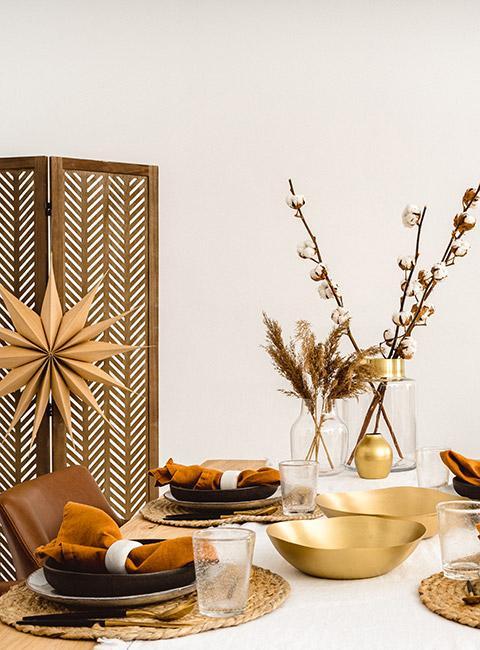 Stół wigilijny nakryty w stylu boho ze złotymi sztućcami i gałązkami bawełny na stole