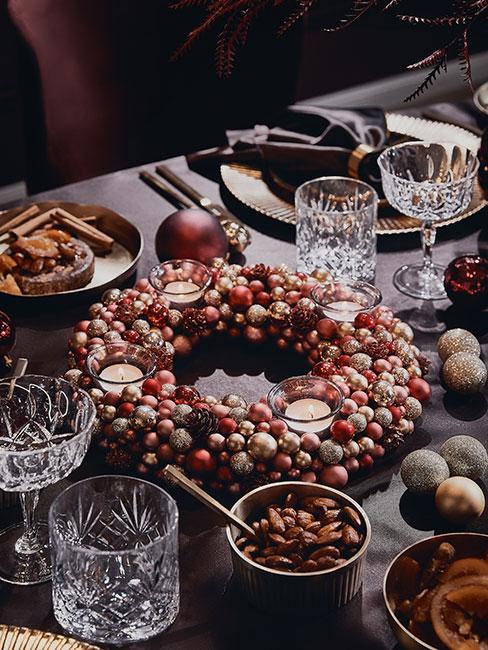 wieniec z jarzębiny i głogu na stole z ciemnym obrusem w stylu barokowym
