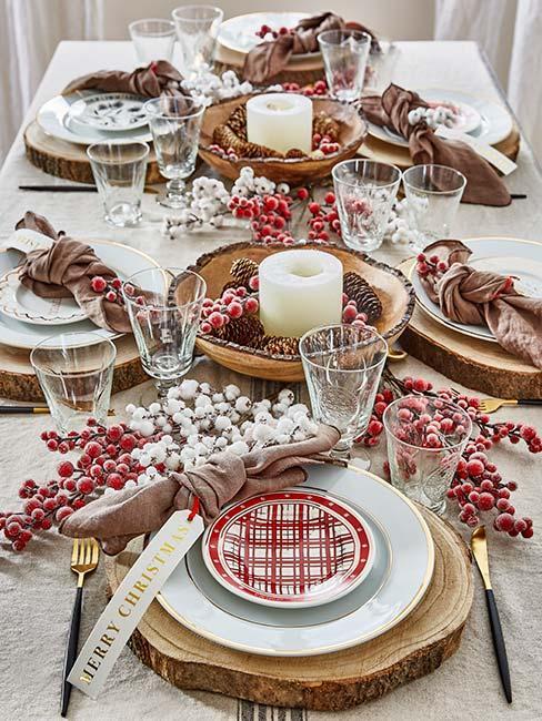 Dekoracja stołu wigilijnegi z jasnym obrusem i dekoracjami w bieli i czerwieni oraz talerzami w szkocką kratę