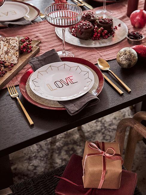 Stół wigilijny z talerzami z napisem love i złotymi sztućcami
