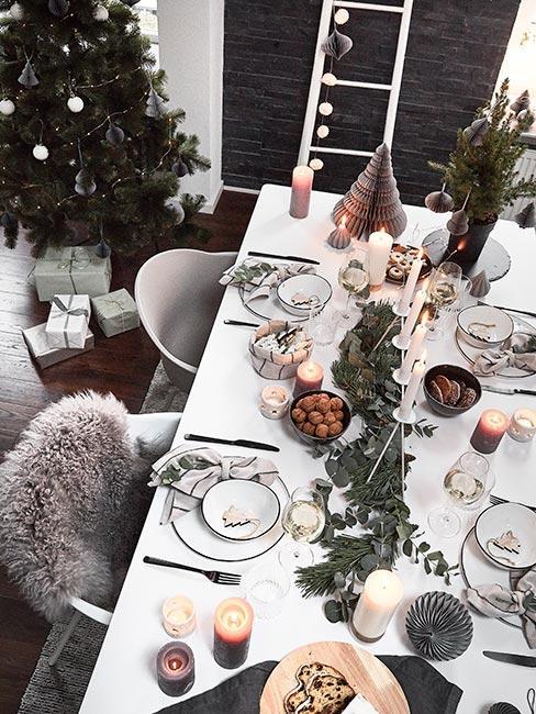 Stół wigilijny w skandynawskim stylu z białą rustykalną zastawą z kamionki, czarnymi sztućcmai i dekoracjami z eukaliptusa