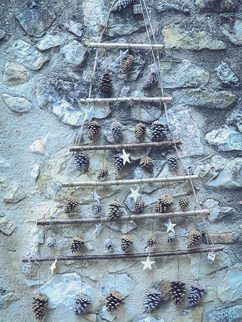 choinka z patyków na ścianie udekorowana szyszkami