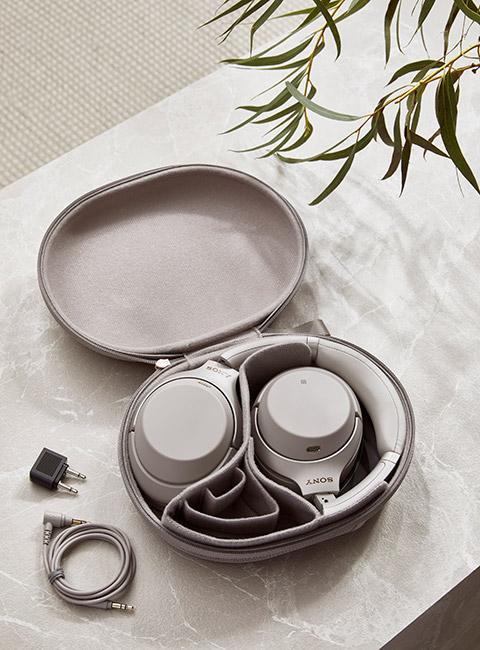 popielate słuchawki złożone w etui na marmurowym stoliku