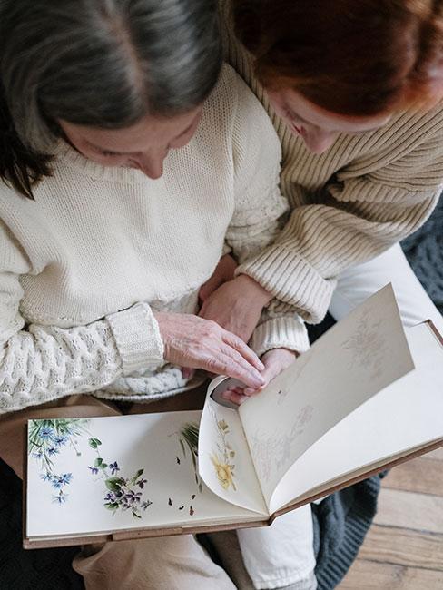 BABcia z córką przeglądają ręcznie robiony album na zdjęcia