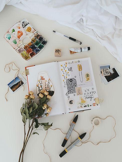Scrapbook na łóżku obok farbek i innych materiałów