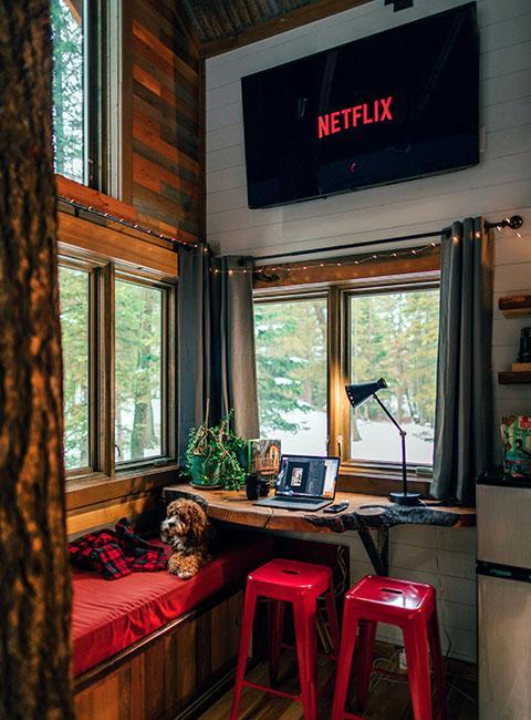 Kącik do oglądania filmów z telewizorem na ścianie i dużymi oknami z widokiem na ośnieżony las