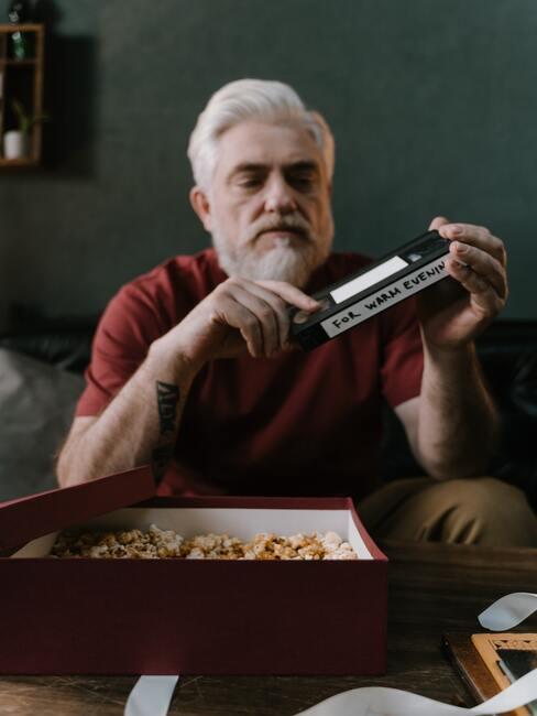 Mężczyzna z białymi włosami i długa siwa brodą odpakowujący prezent
