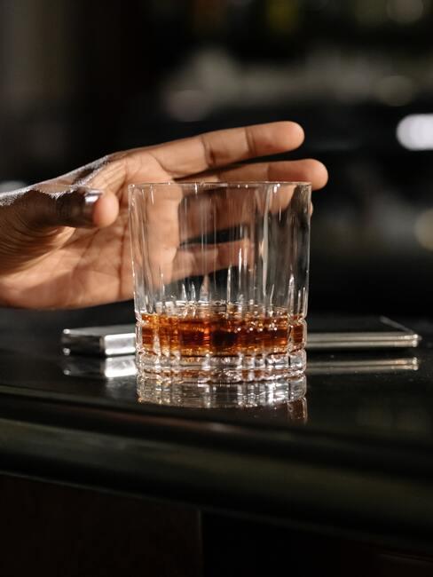 co kupić na dzień chłopaka: męska dłoń trzymająca ozdobną szklankę do whisky w dłoni