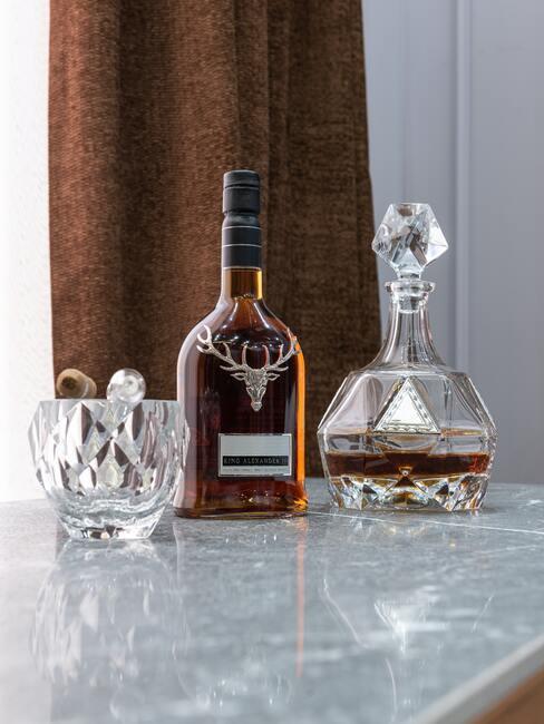 butelka whisky na stole, obok ozdobna karafka i szklanki