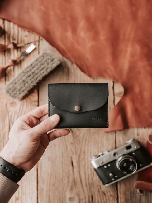 Czarny mały portfel w dłoni mężczyzny na tle drewnianego stołu na którym stoi zabytkowy aparat