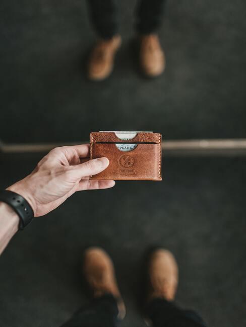Mały brązowy portfel na karty w dłoni mężczyzny