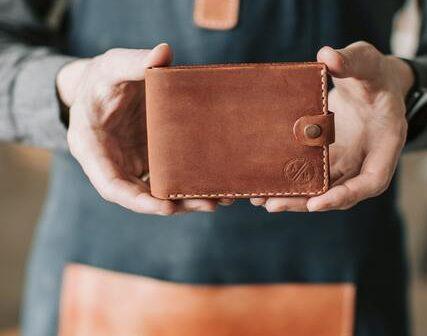 co kupić na dzień chłopaka: Brązowy mały portfel w dłoniach mężczyzny w fartuchu