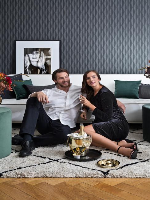 Kobieta i mężczyzna siedzący na dywanie, przed nimi chłodzący się szampan w kubełku z lodem