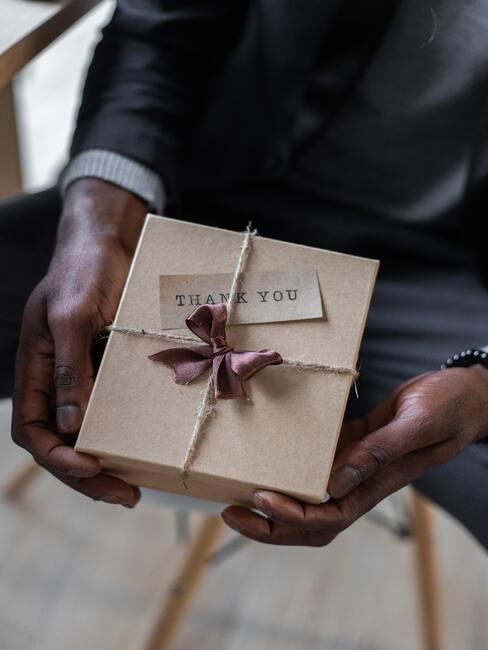 Dłonie mężczyzny w garniturze trzymające prezent